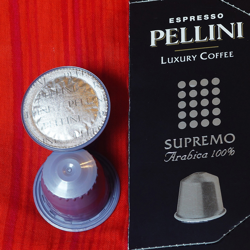 Supremo coffee capsules by Pellini Espresso - violet capsules on a red background