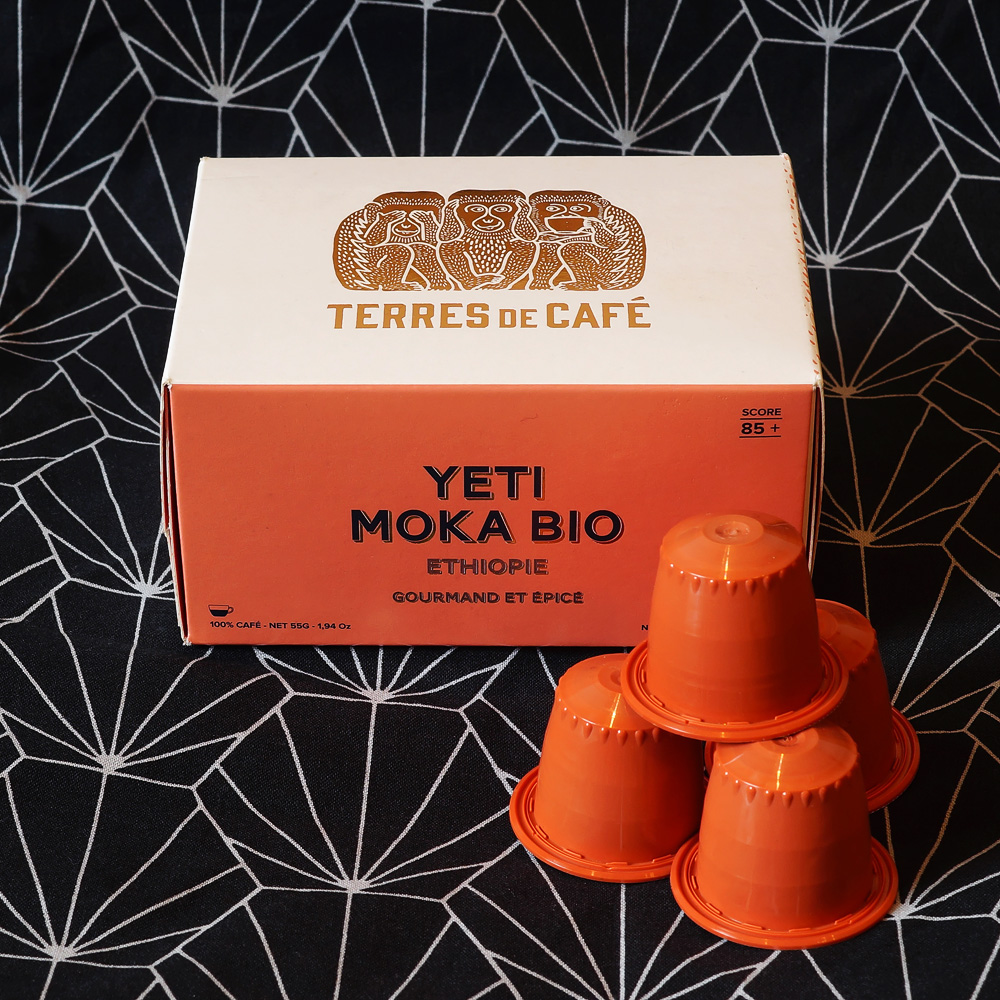 Yeti Moka Bio coffee capsules from Ethiopie by Terres de Café - orange coffee capsules with a box in a dark background