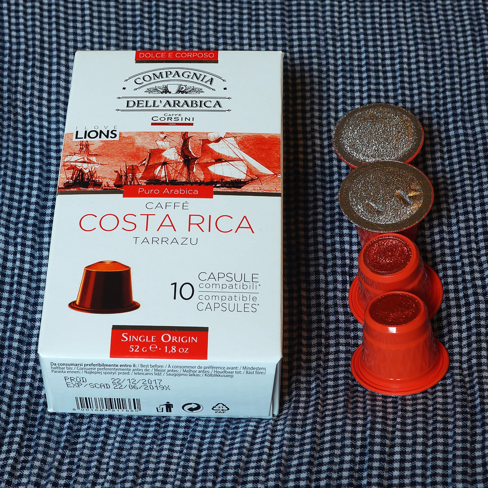 Costa Rica by Caffé Corsini - four red coffee capsules next to the box on a blue background