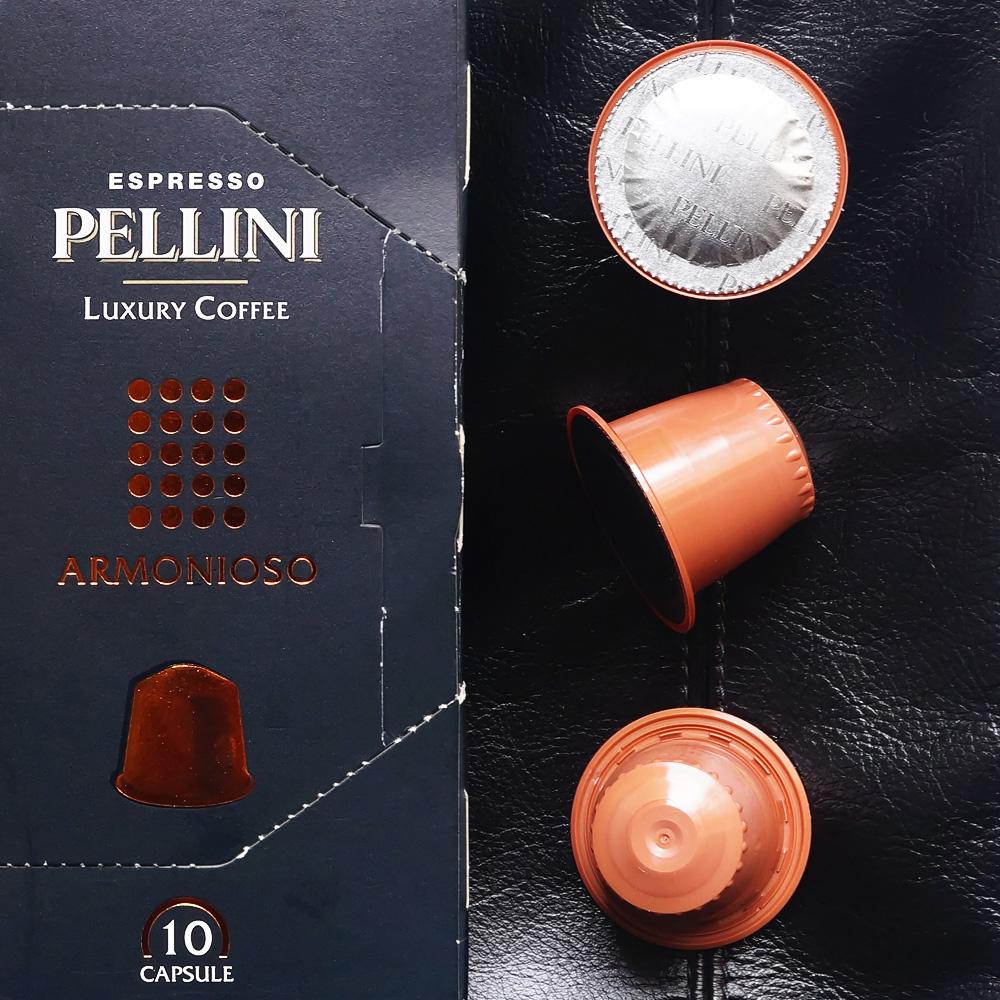 Armonioso by Pellini Espresso - three orange coffee capsules with the box on a black background