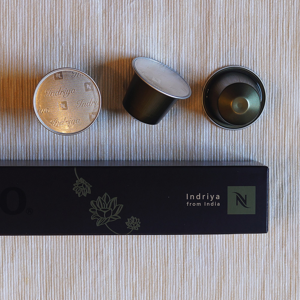 Indriya from India by Nespresso - three black capsules with the box on a pale background