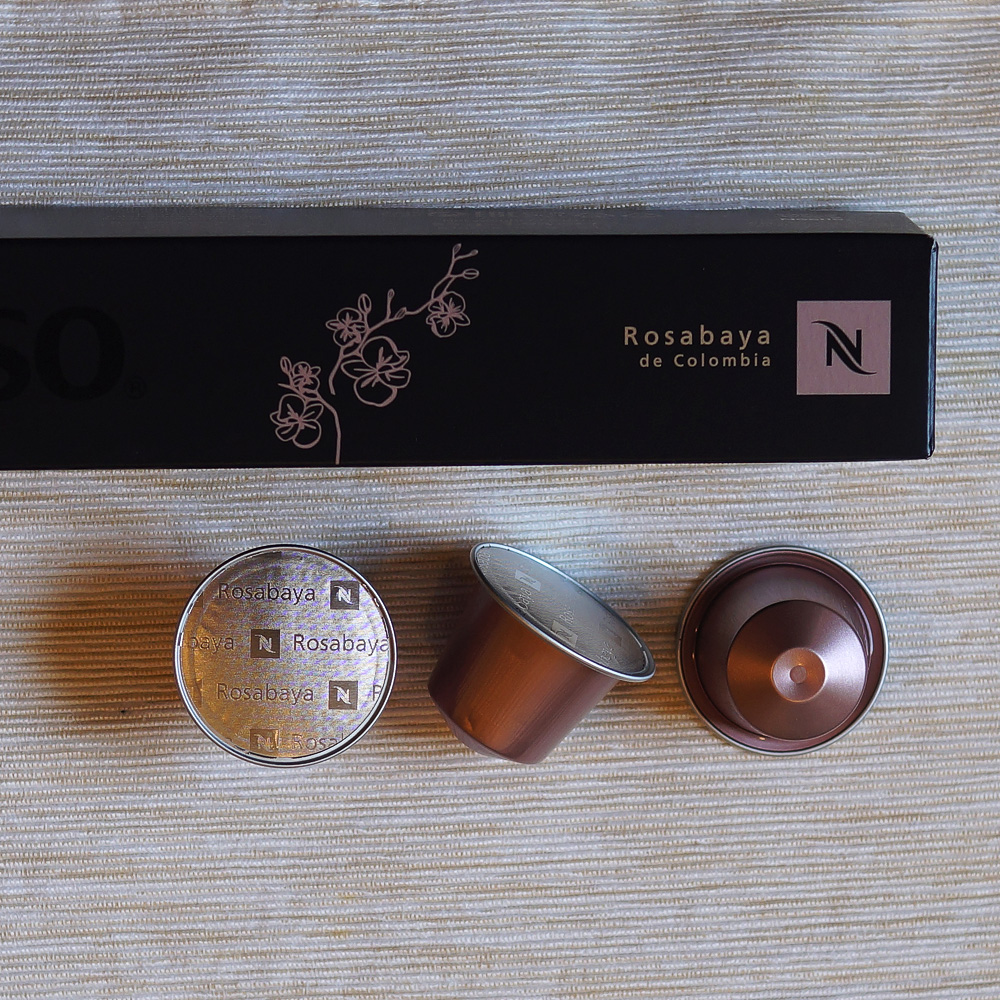 Rosabaya de Colombia by Nespresso - three pale pink capsules wuth black packinging box on light backgound