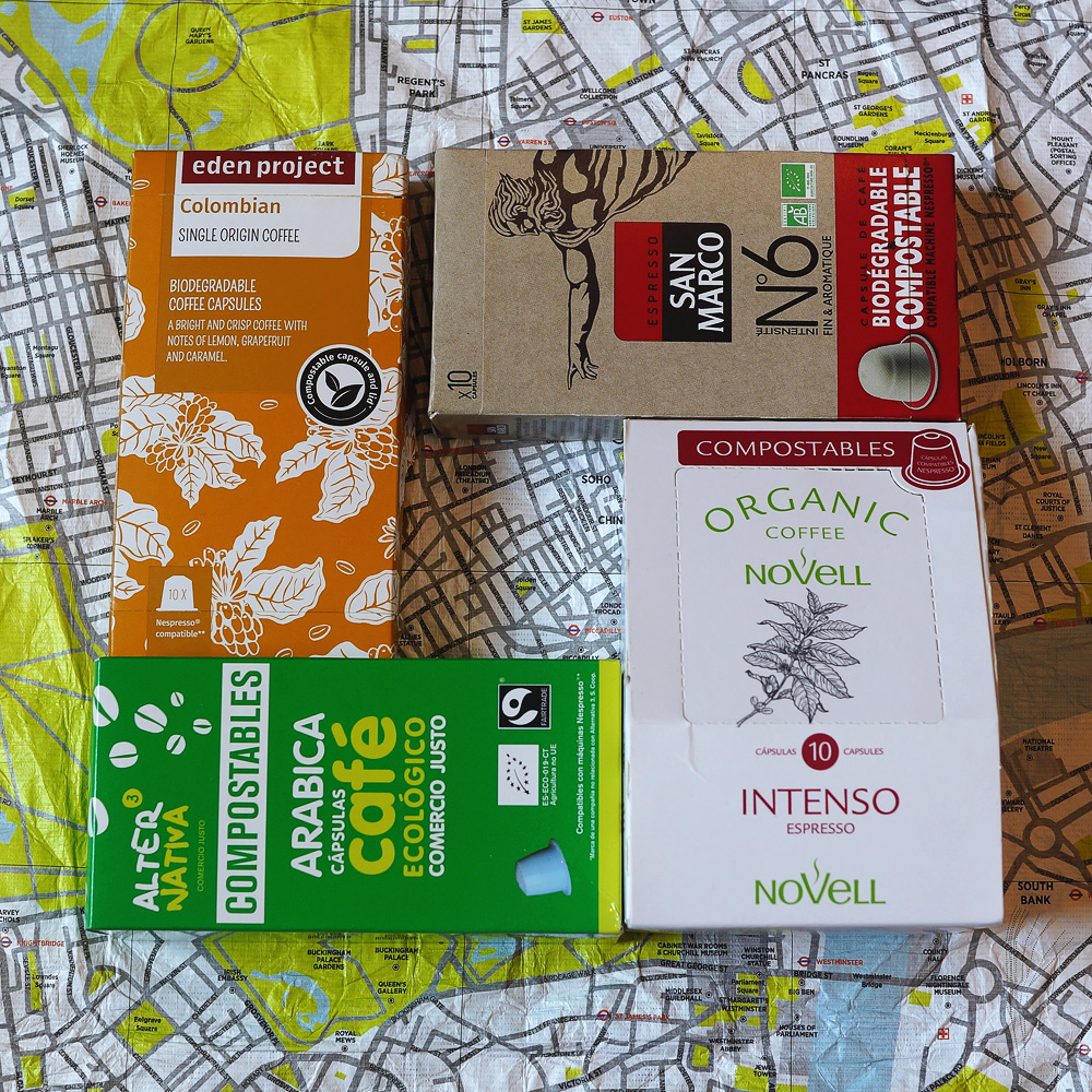 Colourful package boxes of the biodegradable coffee capsules on a map background