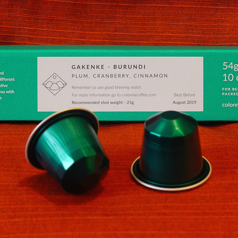 Gakenke by Colonn - two green coffee capsules and a green box on a red background