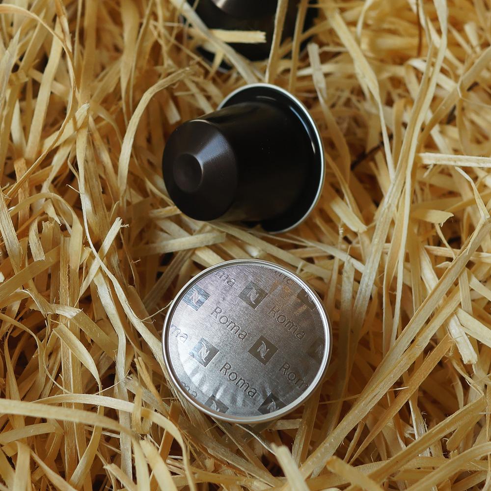 Roma by Nespresso - three black coffee capsules on hay