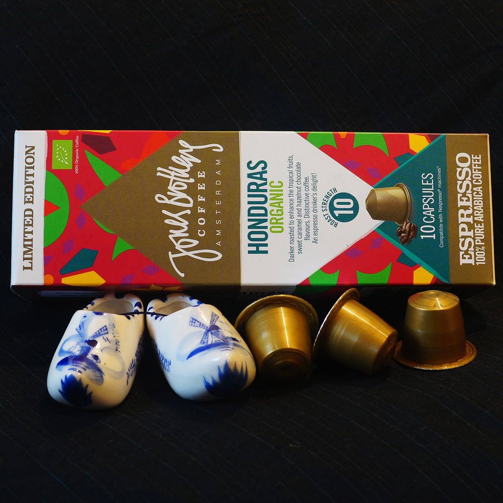 Organic Honduras - golden coffee capsules with the colourful box on a black background