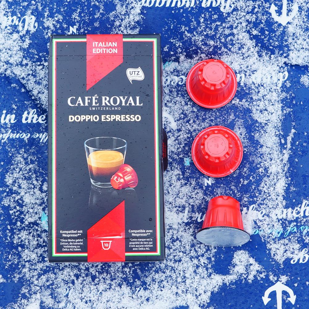 Doppio Espresso by Café Royal - three red coffee capsules and a box on a blue background