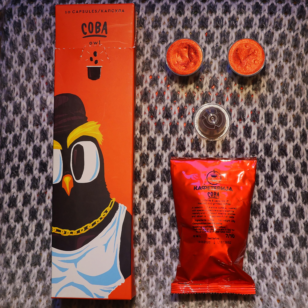 Sova (Owl) by Kafeterija - three coffee capsules with red bag and red box on grey background