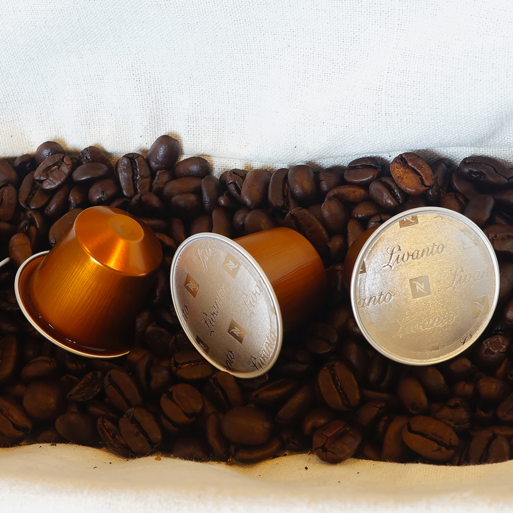 Livanto Nespresso - three orange coffee capsules on coffee bean background