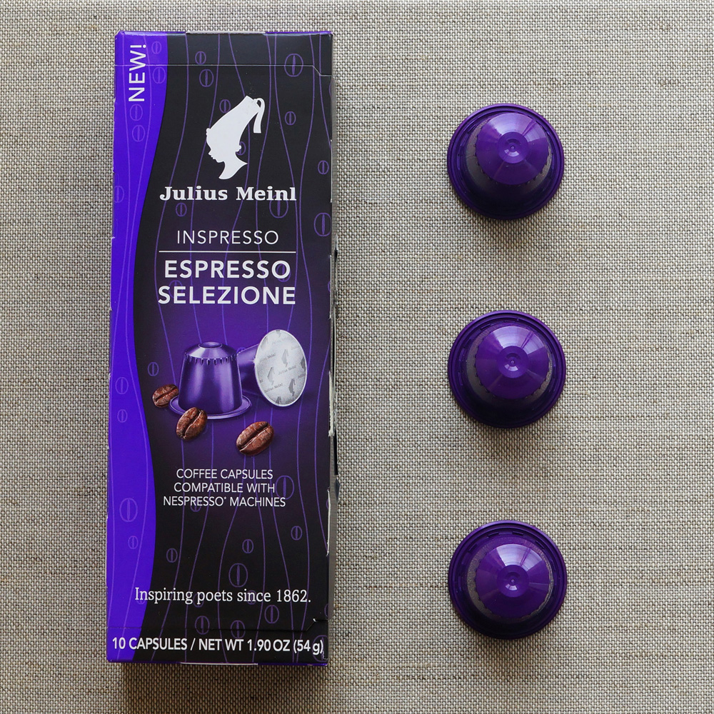 Espresso Selezione by Julius Meinl - three violette coffee capsules with a box on pale background