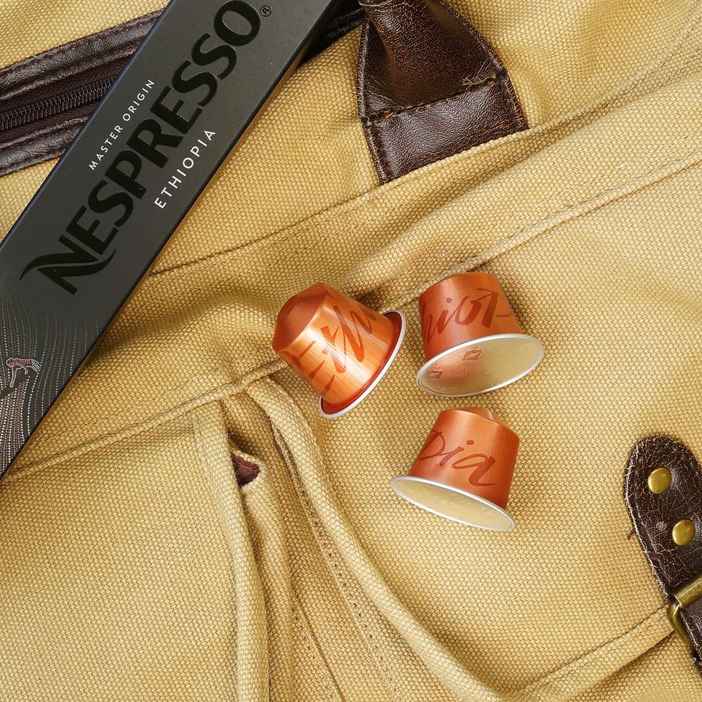 Three orange coffee capsules on a weekender bag
